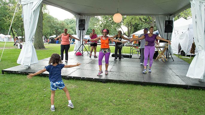 Young girl follows along with a UChicago Medicine zumba class at the African Festival of the Arts in Washington Park