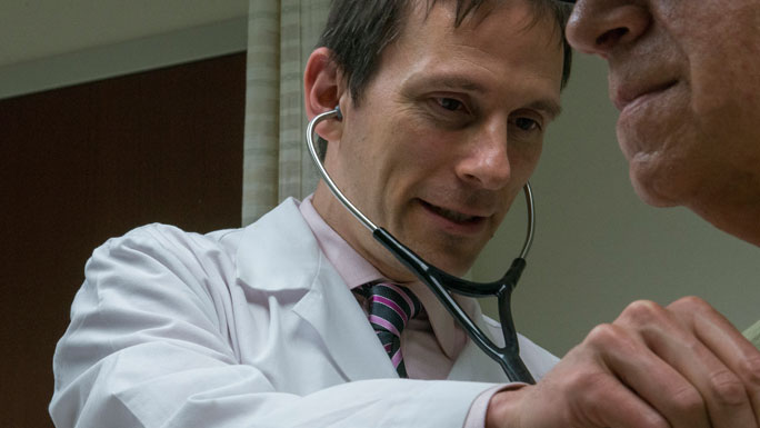 Andrew Artz, MD, medical oncologist, examines a patient