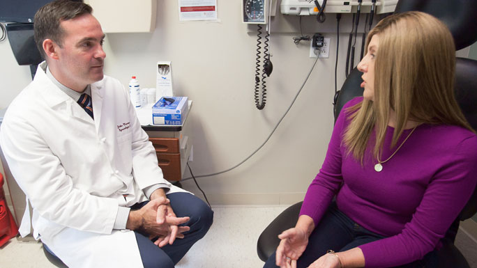Gynecologic oncologist John Moroney, MD, speaks with a patient in clinic