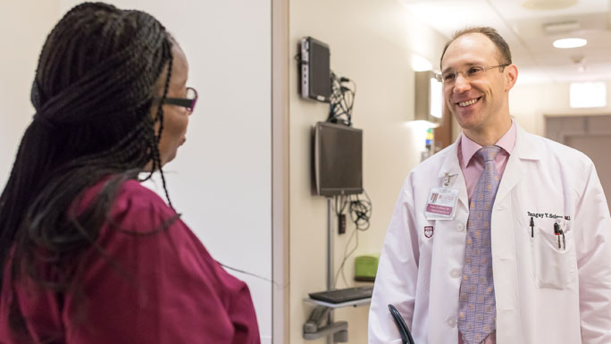 Tanguy Seiwert, MD, medical oncologist, talks with a nurse in clinic