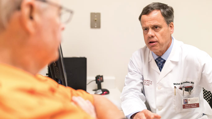 Medical oncologist Walter Stadler, MD, meeting with a patient in clinic