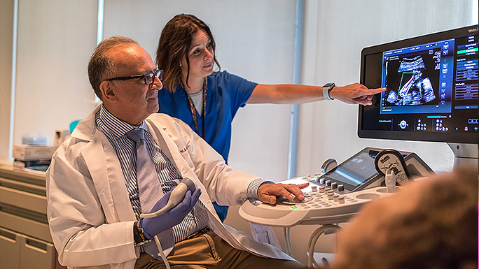 Obstetric ultrasound expert Dr. Jacques Abramowicz and nurse review a patient's during her appoinment