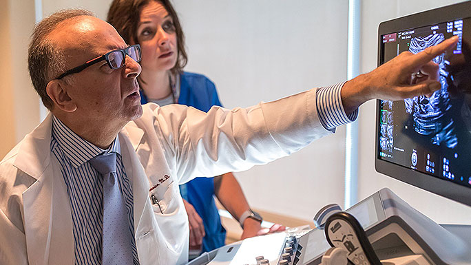 Fetal ultrasound expert Jacques Abramowicz, MD, and nurse reviewing an image on a screen