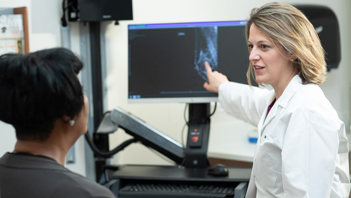 Medical oncologist Olwen Hahn, MD, with patient and CT scan