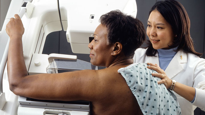 African American woman receiving mammogram, with female Asian tech. NCI image, Rhoda Baer (Photographer)