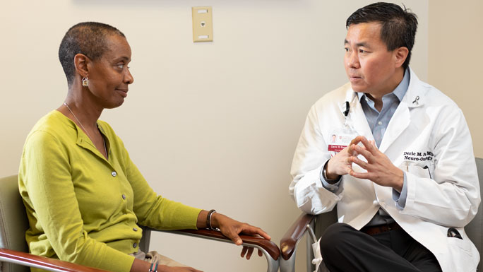 Deric Park, MD, neuro-oncologist, meets with a female patient