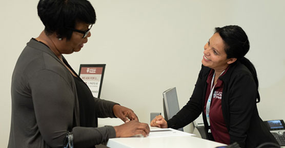 black female patient checking in at DCAM 2F desk