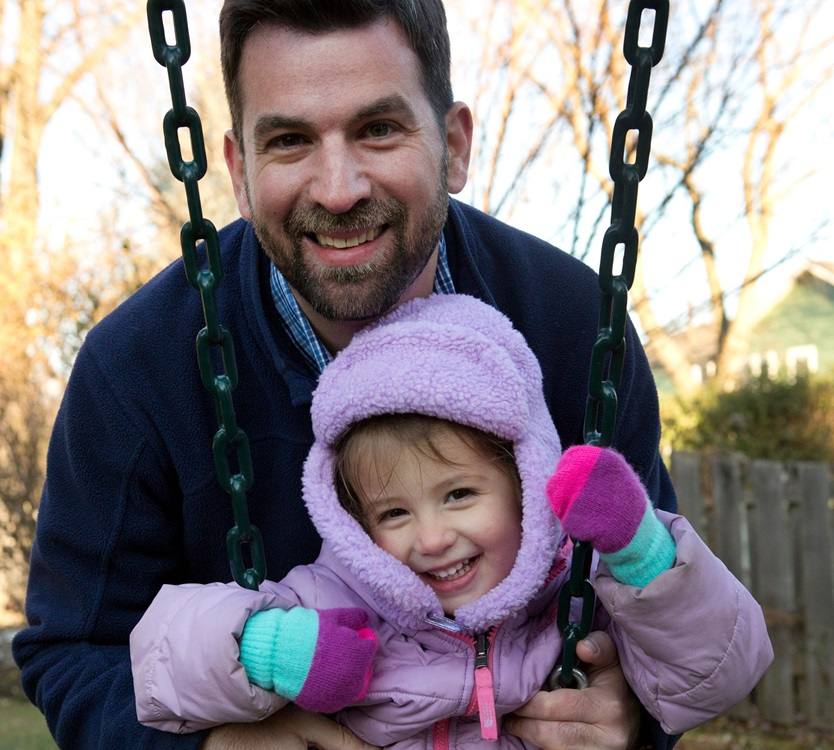 Liver transplant recipient, Brad Goodman, pushing his daughter on a swing