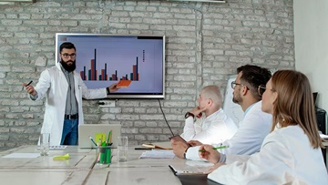 Physicians in lab coats watching a presentation in a conference room.