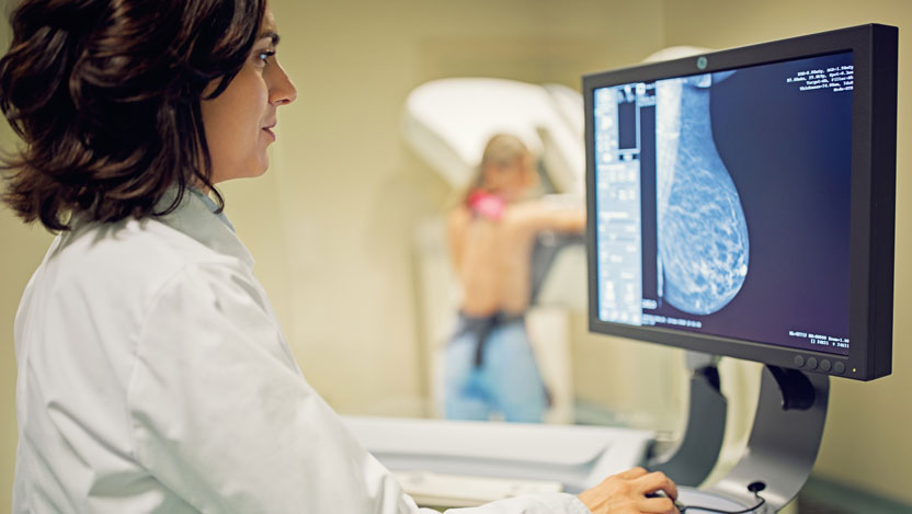 Mammography tech and woman getting mammogram