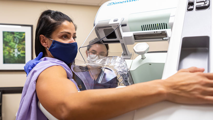 woman in mask receiving mammogram at UChicago Medicine River East Solis Mammography location