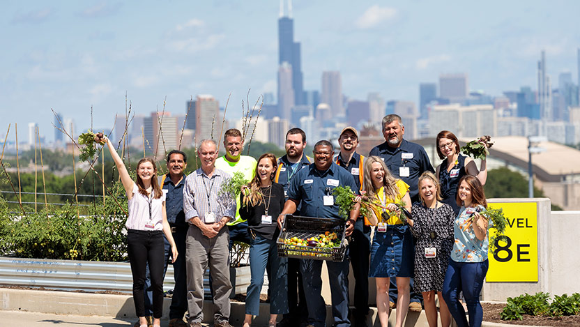 Group photo on top of parking garage with vegetable garden
