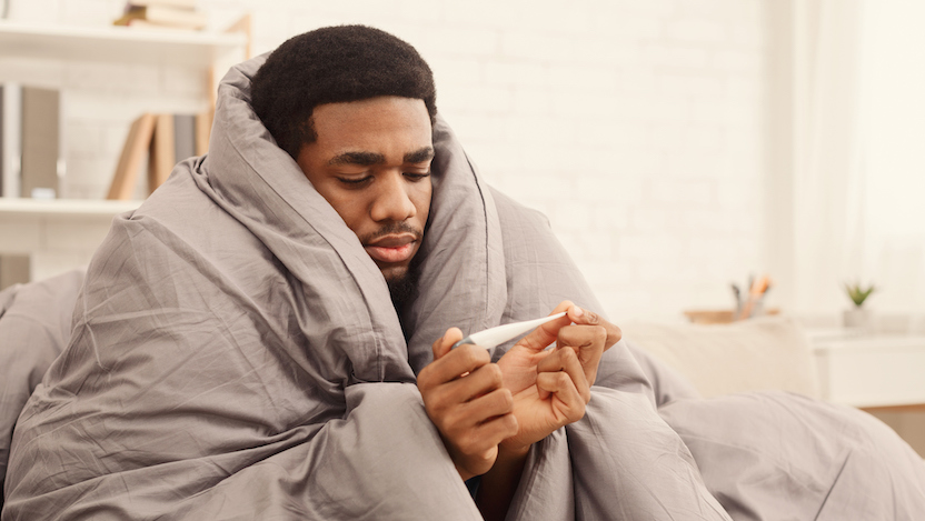 Person wrapped in blanket looking at thermometer