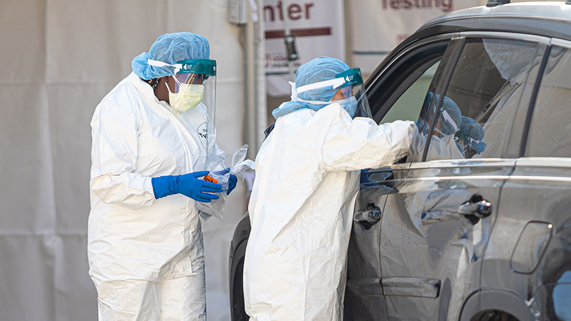 Healthcare workers in PPE testing patients in a car
