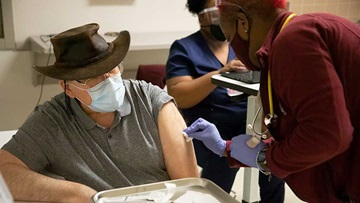 Man in a mask receiving a COVID vaccination injection from a female nurse