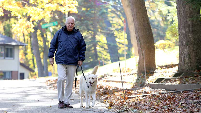 Carl Adams and his dog go on a walk after knee surgery