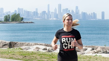 Woman running along the lakeshore path