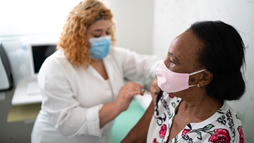A masked nurse applying a vaccine to a masked patient