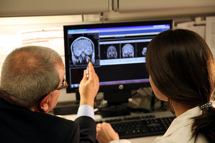 Neurosurgeon and HHT expert Dr. Issam Awad reviewing a neurovascular malformation on a brain scan with program coordinator Shannon Love