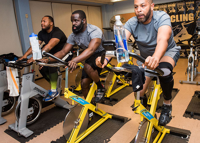 Men cycling in UHI South Side Fit program