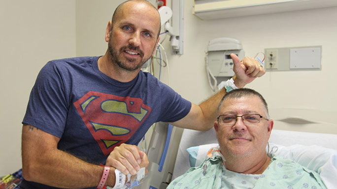 Kidney transplant patient Stewart Botsford (in bed) and his donor, Justin Maduena, visit with each other on August 18, 2016, in Mitchell Hospital after their surgeries two days earlier.