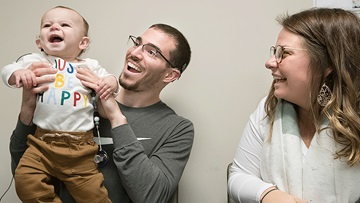 10-month-old Dennis Hill, post cochlear implant activation, with his dad, Michael Hill, and mom Jenna Jones