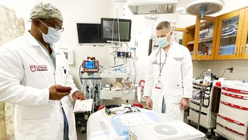 Kenneth Wilson, MD, works with Lt. Col. Timothy Plackett, DO, a trauma surgeon from the U.S. Army.