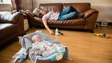 Mom napping on couch while newborn naps in sleeper