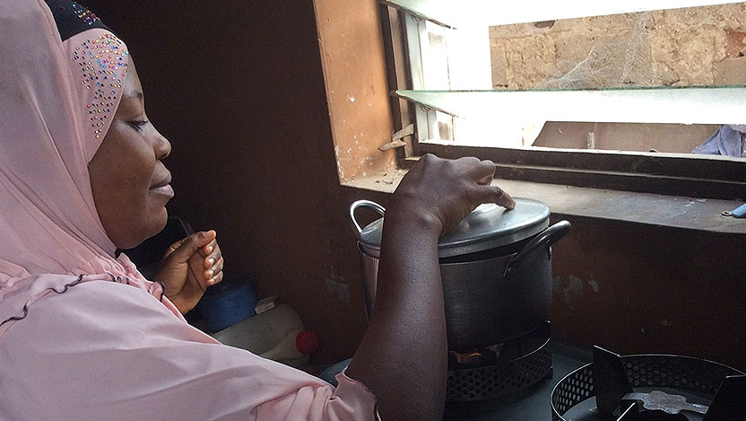 A nigerian woman cooking at a stove