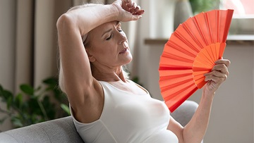 Woman fanning herself during a menopausal hot flash