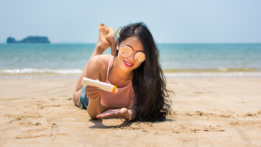Woman on the beach applying sunscreen