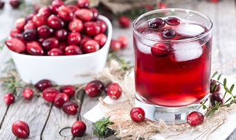 A bowl of cranberries and a glass of cranberry juice