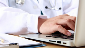 Doctor typing on a laptop