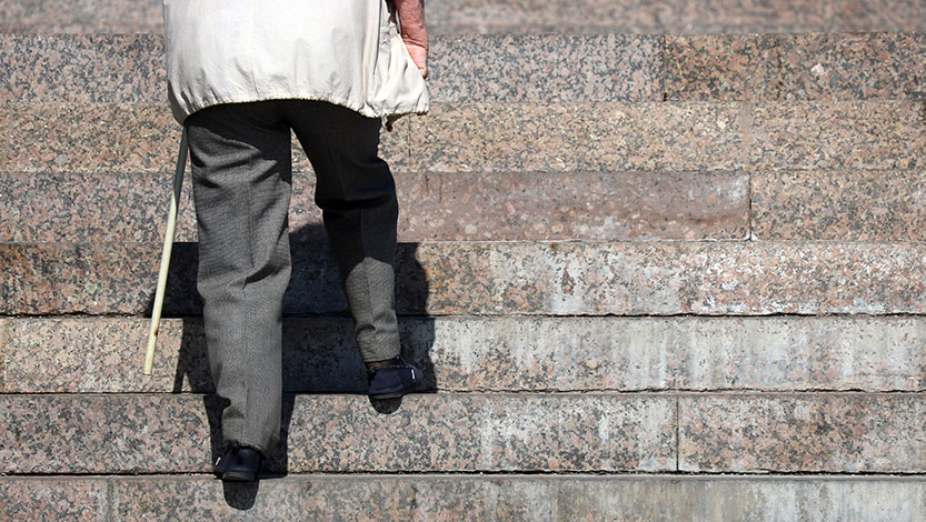 Elderly person walking up stairs