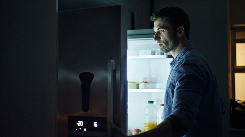 Man looking in refrigerator at night