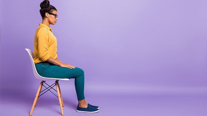 Woman sitting in chair on purple background