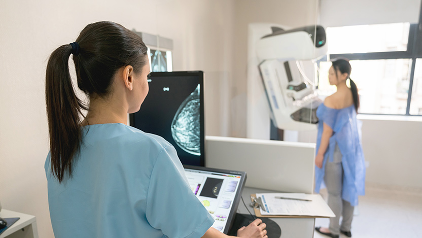Nurse giving mammogram exam to standing patient