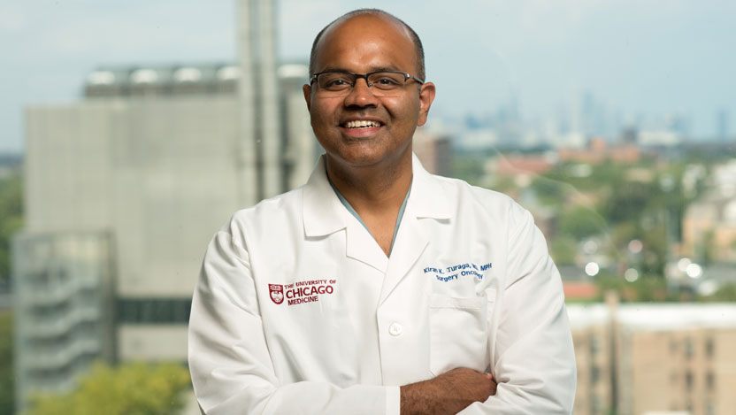 Kiran Turaga, MD, MPH, in front of window overlooking Chicago skyline from Center for Care and Discovery