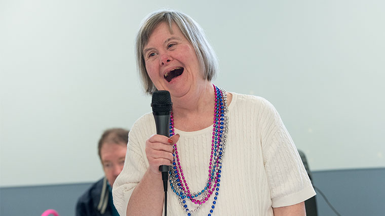 Image of a Misericordia resident singing into a microphone