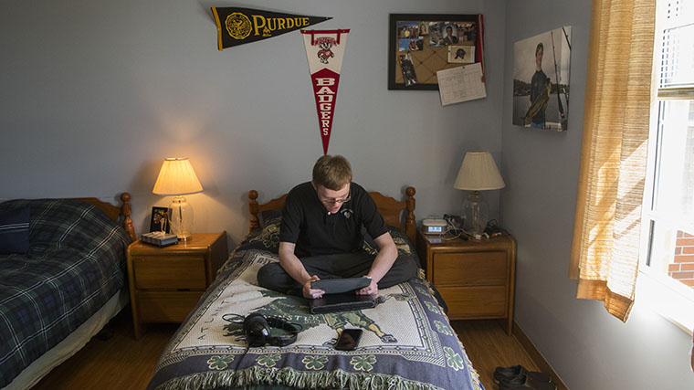 Image of a Misericordia resident in his bedroom looking at a photo in his hands