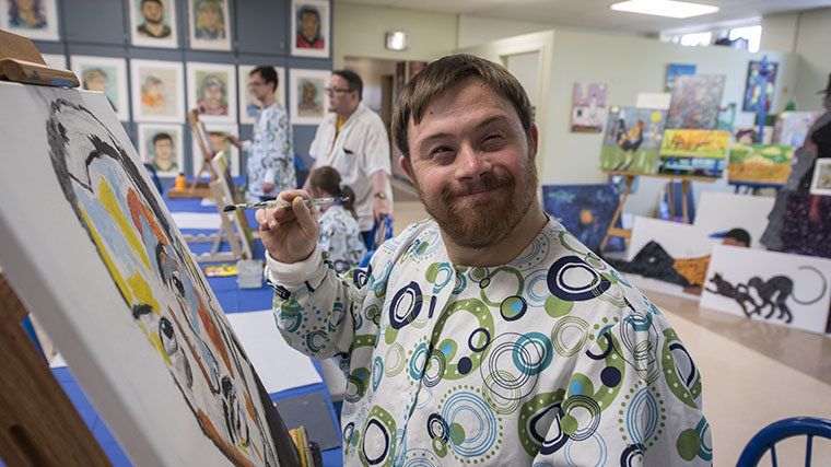 Image of a smiling Misericordia resident painting