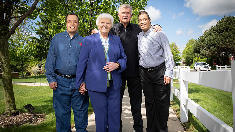 Mike Ditka standing with Misericordia Executive Director Sister Rosemary Connelly and two residents