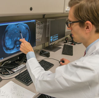 Xavier Keutgen, MD, pointing at scan on computer monitor