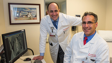 David Rubin, MD, and Russell Cohen, MD, in an office with a computer