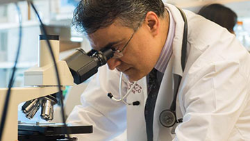 Dr. Akash Patnaik looking into a microscope