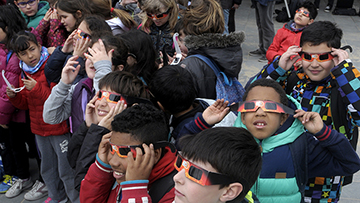 Children watch a solar eclipse with safety glasses