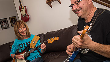 Jean Martinez plays guitar with her husband after treatment for Parkinson
