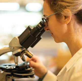 Female cancer researcher looking in microscope