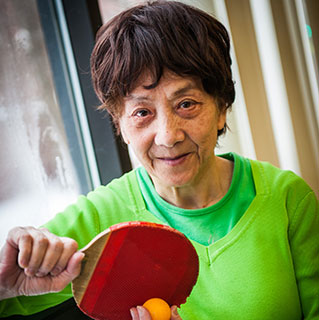 Parkinson's disease patient Cheng Xiu Xu, who was treated by physicians Tao Xie, MD, PhD, and Peter Warnke, MD, plays ping pong at her apartment building