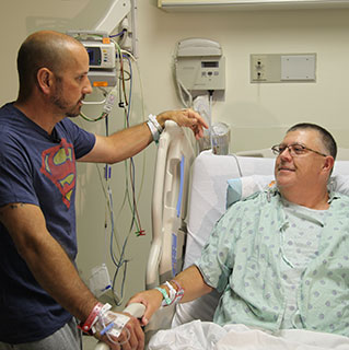 Kidney transplant patient Stewart Botsford (in bed) and his donor, Justin Maduena, visit with each other in Mitchell Hospital after their surgeries two days earlier.